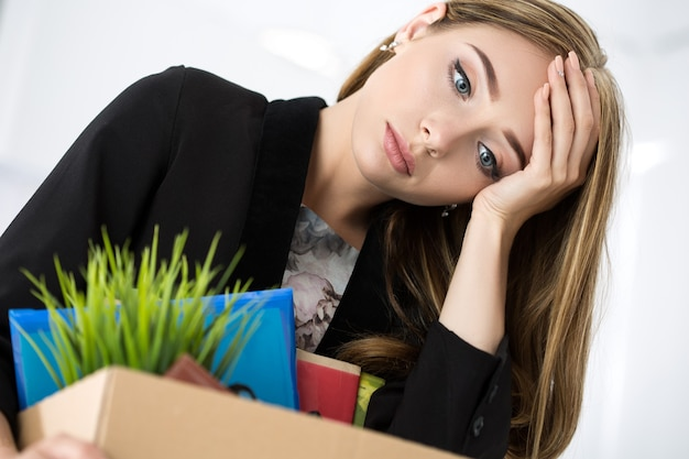 Młoda zwolniona pracownica w biurze trzymając karton z jej dobytkiem. wywalanie koncepcji.
