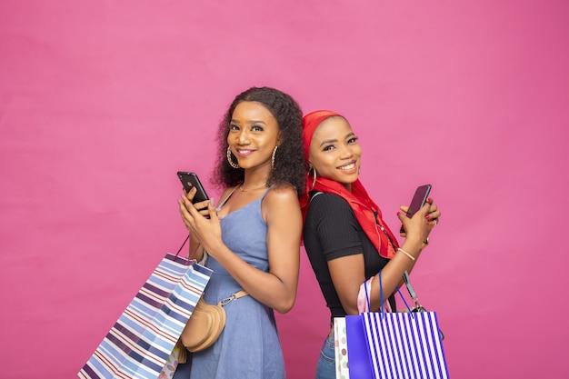 Młode afrykańskie panie oglądają coś na swoich telefonach komórkowych, niosąc torby z zakupami