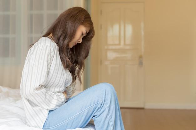 Młode azjatki mają silny ból brzucha. koncepcja zdrowia i chorych.