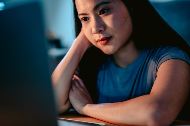Młode azjatki pracujące z laptopem w salonie w domu w ciemności przy lampiepraca z domu