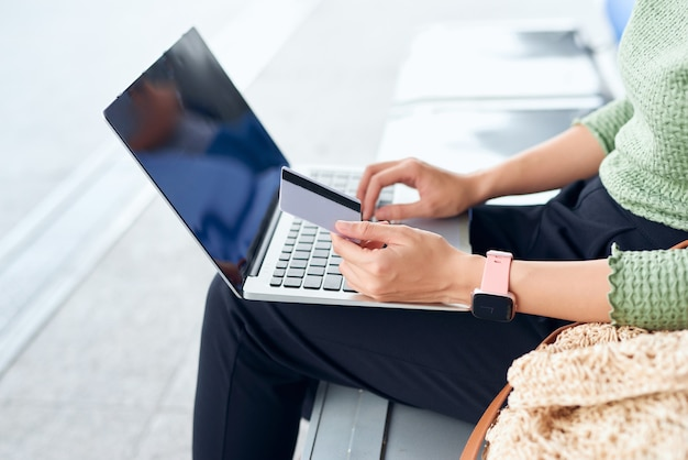 Młode azjatki trzymające kartę kredytową i korzystające z laptopa robiące zakupy online podczas sprawdzania lotu lub odprawy online na lotnisku