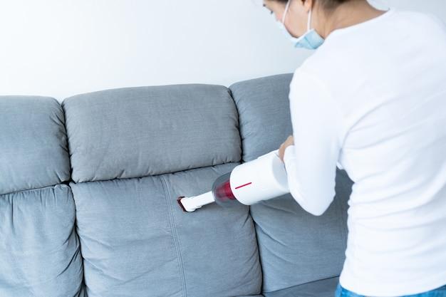 Młode azjatki w masce i korzystające z bezprzewodowego odkurzacza do czyszczenia sofy w salonie