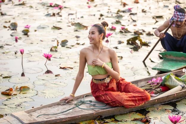 Młode azjatki w tradycyjnych strojach w łodzi i różowe kwiaty lotosu w stawie. piękne dziewczyny w tradycyjnych strojach. tajski. kulturalny