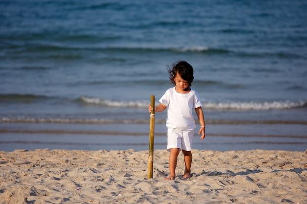 Młode azjatyckie dziecko spacerujące po tropikalnej plaży