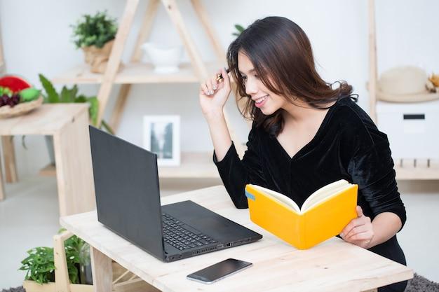Młode azjatyckie kobiety biznesu pracujące z laptopem komputerowym i piszące na notesie