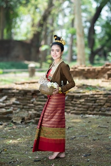 Młode azjatyckie kobiety w tradycyjny strój stojący na starej ścianie z kokardą lotosu w ręku. piękne dziewczyny w tradycyjnych strojach. tajska dziewczyna w retro sukienka tajski.