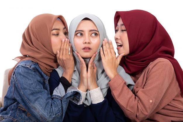 Młode azjatyckie zawoalowane kobiety były zszokowane, gdy jej przyjaciel szeptał siedząc