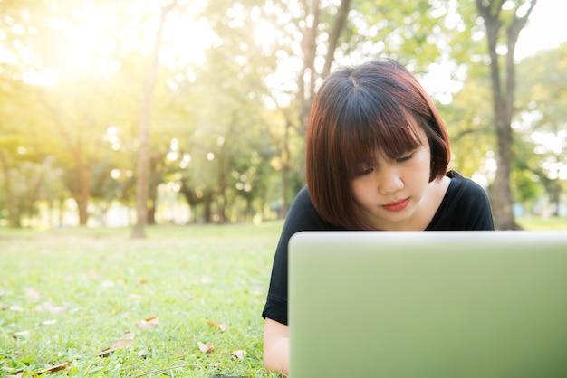 Młode azjatykcie kobiet nogi na zielonej trawie z otwartym laptopem