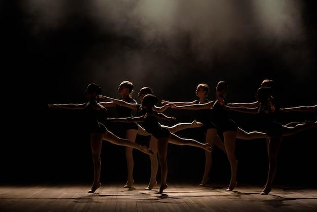 Młode baleriny ćwiczą w klasie baletowej. wykonują różne ćwiczenia choreograficzne i stoją w różnych pozycjach.