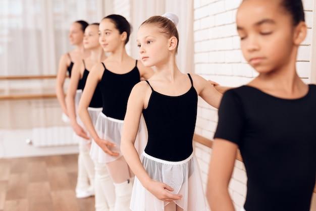 Młode baleriny ćwiczą w klasie baletowej.