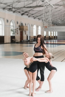 Młode baleriny dziewcząt stojących wokół nauczyciela w klasie tanecznej