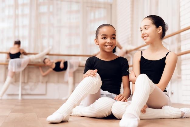 Młode baleriny odpoczywają podczas przerwy w lekcjach baletu.