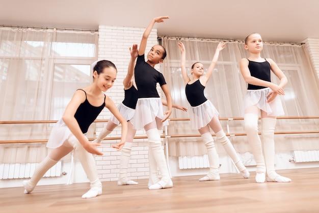 Młode baleriny próbują w klasie baletowej.