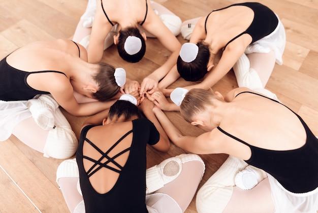 Młode baletnice wykonują różne ćwiczenia choreograficzne.