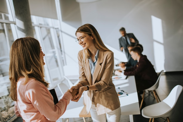 Młode biznesowe kobiety daje życzliwemu uściskowi dłoni w biurze