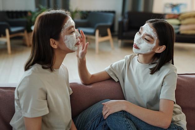 Młode bliźniaczki z glinianą maską na twarz, siedząc na kanapie przed kamerą w domu, podczas gdy jedna z nich dotyka twarzy swojej siostry