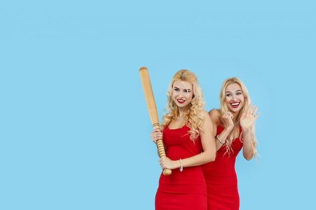 Młode blond kobiety w modnych czerwonych sukniach trzymają kij bejsbolowego lub kant, kopii przestrzeń.