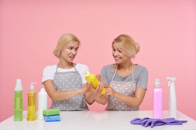 Młode blond piękne gospodynie domowe w gumowych rękawiczkach podczas przygotowań do wiosennych porządków