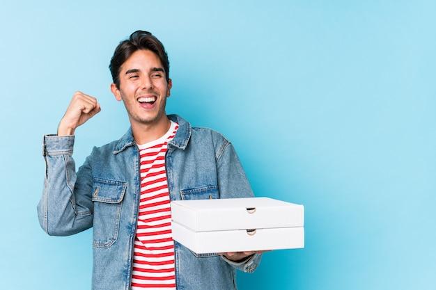 Młode caucasian mężczyzna mienia pizze odizolowywał dźwiganie pięść po zwycięstwa, zwycięzcy pojęcie.