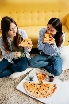 Młode chłodzące kobiety cieszy się pizzę