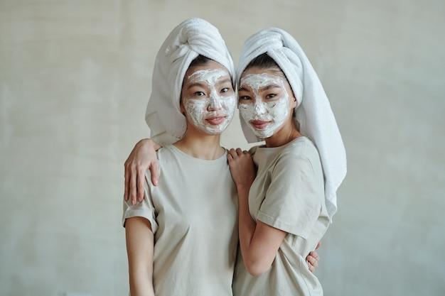 Młode czułe bliźniaczki z ręcznikami na głowach i glinianą maską na twarz stojące przed kamerą, podczas gdy jedna z nich obejmuje swoją siostrę