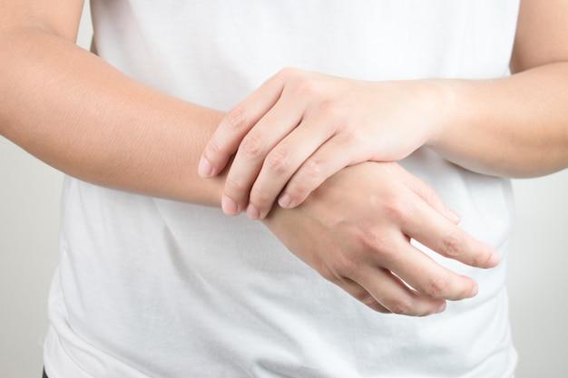 Młode dłonie trzymające drugą stronę nadgarstka.
