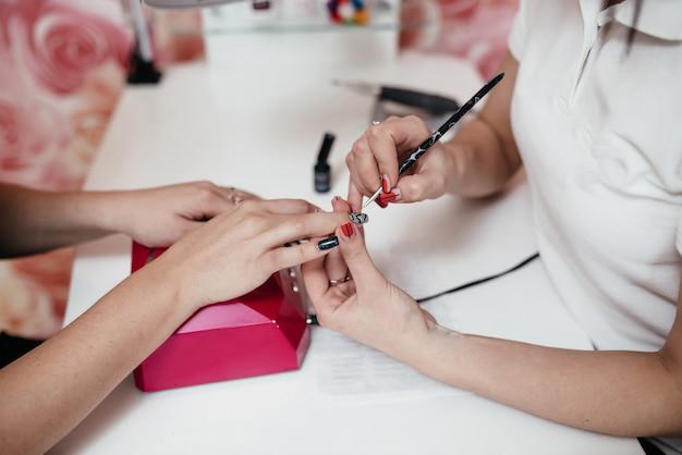 Młode, doskonałe, zadbane dłonie kobiety z różowymi i białymi butelkami lakieru do paznokci.