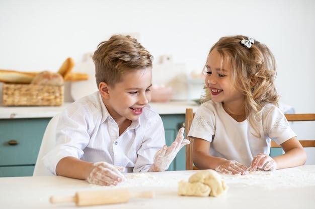 Młode dzieci bawić się podczas gdy gotujący ciastka w kuchni wpólnie