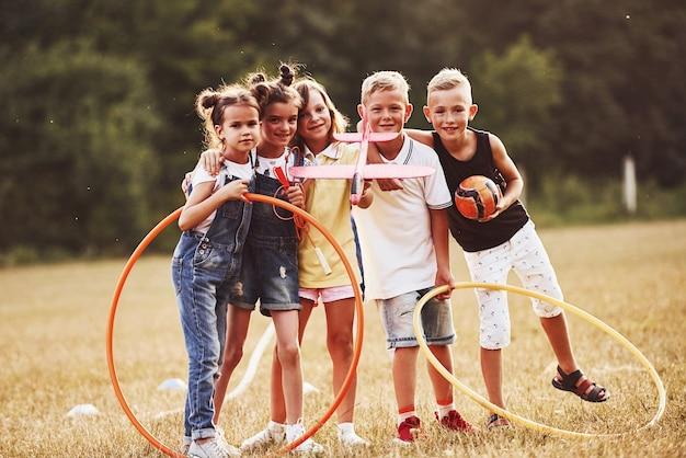 Młode dzieci z piłki nożnej, samolot zabawka i okręgi fitness stoi razem w polu w słoneczny dzień.
