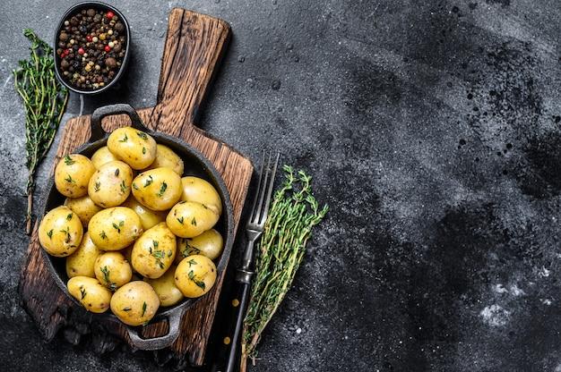 Młode dziecko gotowane ziemniaki z masłem na patelni. czarne tło. widok z góry. skopiuj miejsce.