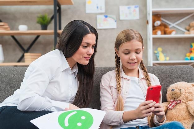 Młode dziecko psycholog patrzeje telefon komórkowego chwyt małą dziewczynką