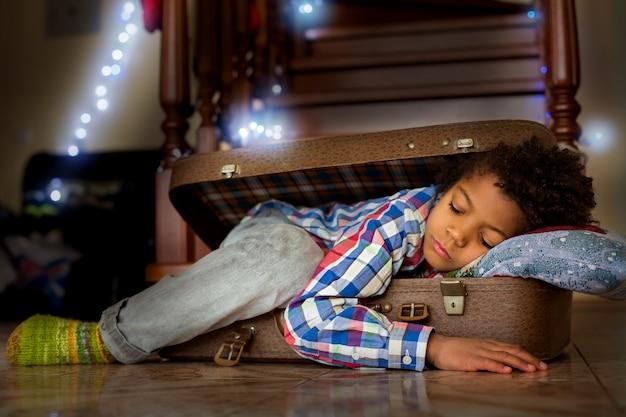 Młode dziecko śpi wewnątrz walizki. ładny chłopak śpi w walizce. nie mogłem sięgnąć do łóżka. gdzieś w rodzinnym domu.
