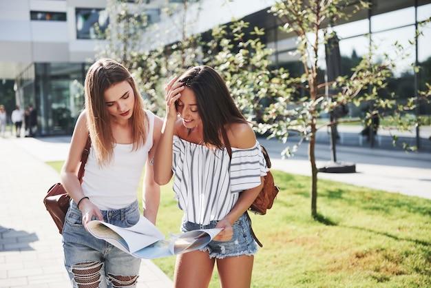 Młode dziewczyny czytają mapę miasta i szukają hotelu. cudowni turyści z plecakami określają pojęcie wiedzy o świecie.