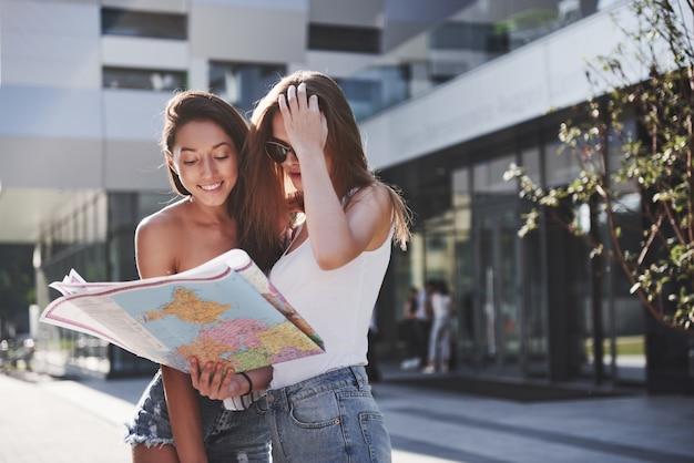 Młode dziewczyny czytają mapę miasta i szukają hotelu. urocze turyści z plecakami określają pojęcie wiedzy o świecie