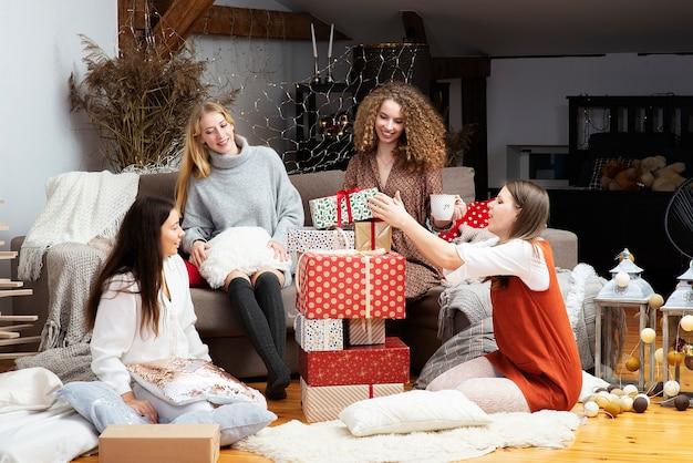 Młode dziewczyny dobrze się bawią, pakują prezenty w domu, praca zespołowa przyjaciół pakuje prezenty na boże narodzenie