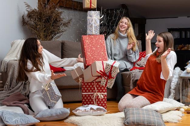 Młode dziewczyny dobrze się bawią, pakują prezenty w domu, świetna praca zespołowa przyjaciół pakujących prezenty na boże narodzenie, przygotowują się na nadchodzący nowy rok i boże narodzenie