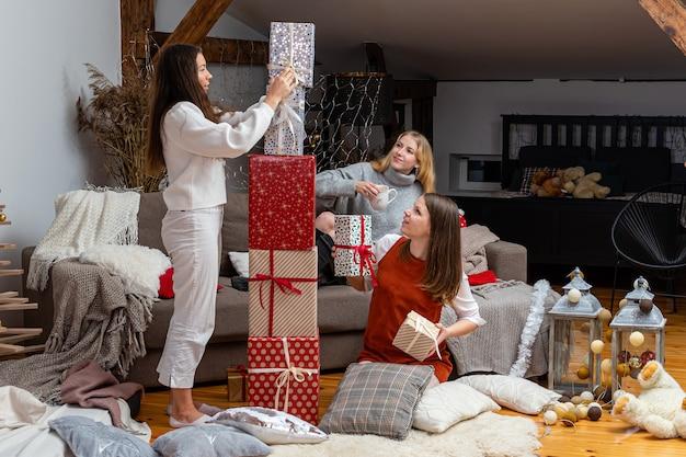 Młode dziewczyny dobrze się bawią, pakują prezenty w domu, świetna praca zespołowa przyjaciół pakujących prezenty na boże narodzenie