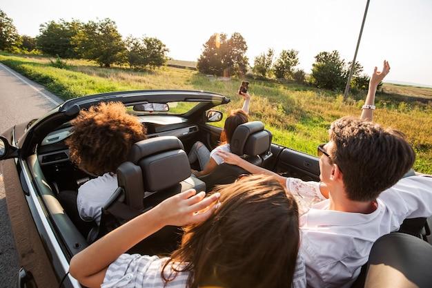 Młode dziewczyny i chłopaki siedzą w czarnym kabriolecie i robią selfie w ciepły słoneczny dzień. .