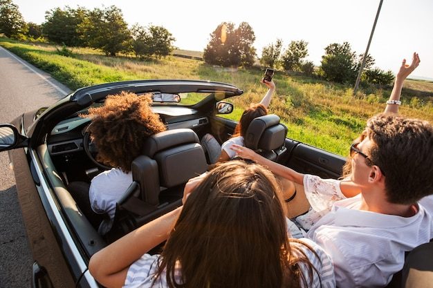 Młode dziewczyny i chłopaki siedzą w czarnym kabriolecie i robią zdjęcie przez telefon o zachodzie słońca.