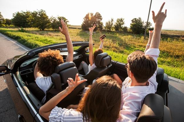 Młode dziewczyny i chłopaki siedzą w czarnym kabriolecie, trzymając ręce w górze i robią selfie w ciepły słoneczny dzień. .