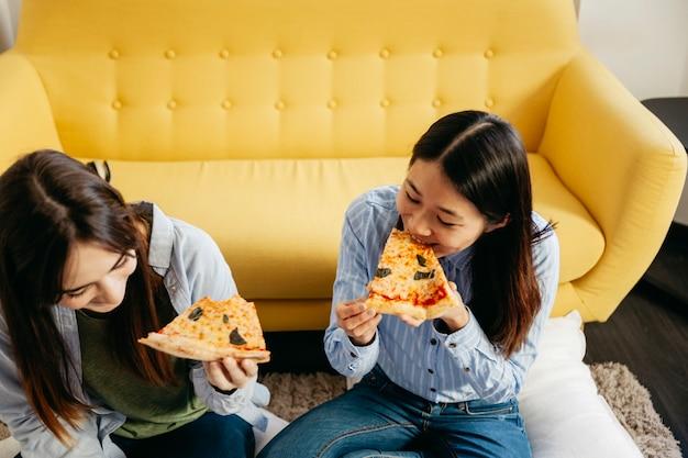 Młode dziewczyny je pizzę w domu