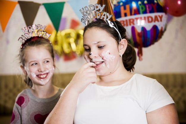 Młode dziewczyny ma zabawę przy przyjęciem urodzinowym