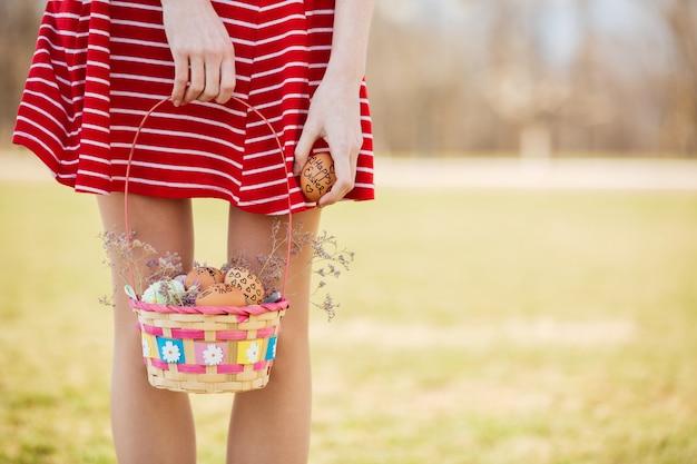 Młode dziewczyny nogi i kosz z malowane pisanki na zewnątrz