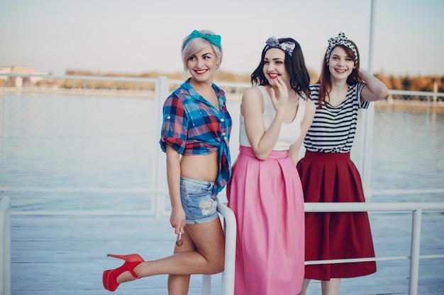 Młode dziewczyny pozują na balustrada z portem morskim i jednym z uniesioną nogą