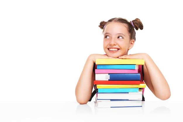 Młode dziewczyny pozują ze stosem książek na białym tle