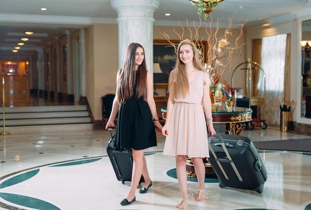 Młode dziewczyny przy recepcji w hotelu, młode dziewczyny przychodzą do hotelu.