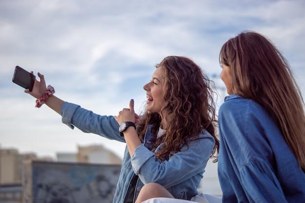 Młode dziewczyny robiące selfie w skateparku pod słońcem i pochmurnym niebem