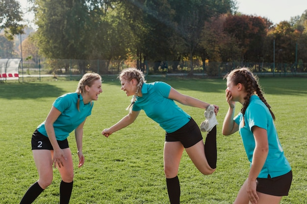 Młode dziewczyny rozgrzewają się na boisku piłkarskim