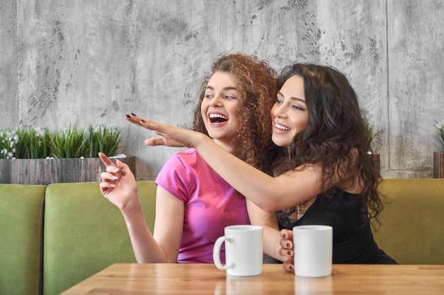 Młode dziewczyny siedzą w kawiarni i plotkują podczas picia herbaty