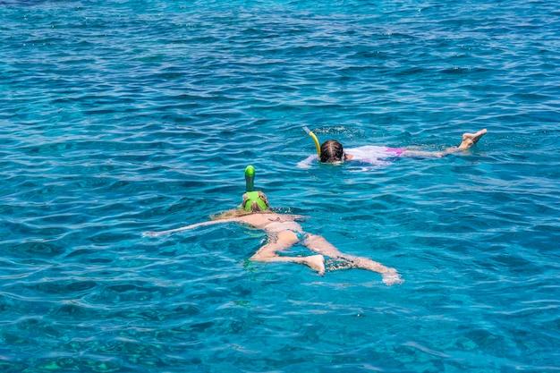 Młode dziewczyny snorkeling w niebieskich czystych wodach nad rafą koralową na morzu czerwonym w sharm el sheikh, egipt. koncepcja podróży i stylu życia. widok z góry. dwóch snorkelerów pływa w turkusowej wodzie